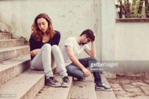 Young People With Problems Sitting At The Staircase
